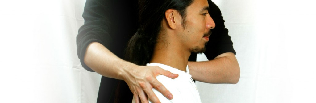 Alexander technique teacher applying positioning to man's shoulders