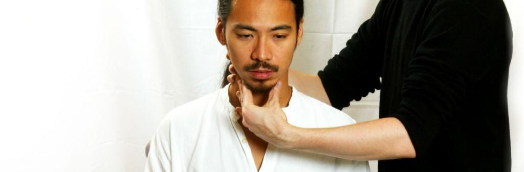 Alexander technique teacher applying positioning to man's neck